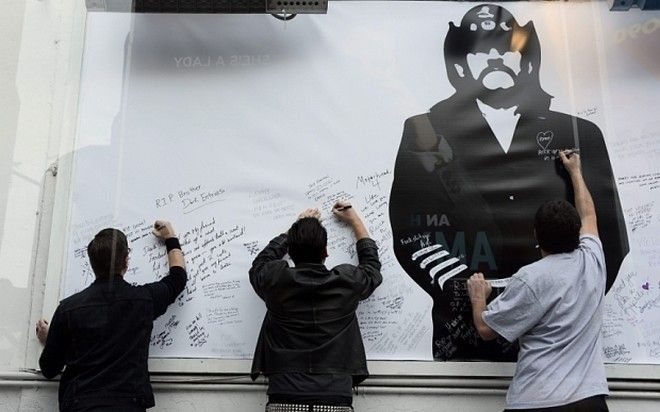 epa05094822 Fans of British metal band Motorhead sign a giant memorial to Lemmy at the Rainbow Bar and Grill in Hollywood, California, USA, 09 January 2016. The Rainbow, purportedly Lemmy's favorite bar, allowed fans to come in and celebrate the rocker's life.  EPA/PAUL BUCK