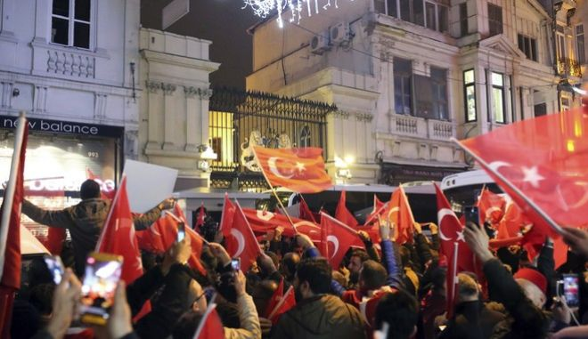 """Supporters of Turkey's President Recep Tayyip Erdogan wave flags outside the Dutch consulate during a protest, in Istanbul, early Sunday, March 12, 2017. Turkey and the Netherlands sharply escalated a dispute between the two NATO allies on Saturday as the Dutch withdrew landing permission for the Turkish foreign minister's aircraft, drawing Turkish President Recep Tayyip Erdogan to call them """"fascists"""". (AP Photo)"""