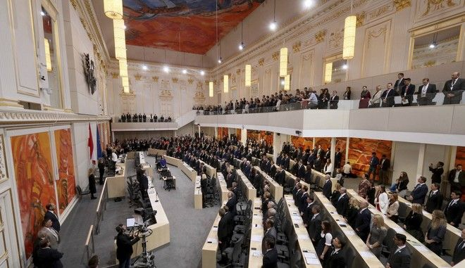 Lawmakers stand during the first session of the national assembly after election at the parliament in Vienna, Austria, Thursday, Nov. 9, 2017. (AP Photo/Ronald Zak)