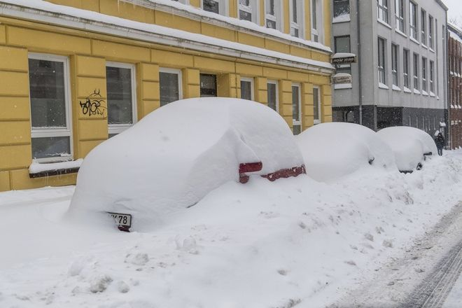 Snow-covered cars are parked in a street in Flensburg, Germany Thursday, March 1, 2018.  (Benjamin Nolte/dpa via AP)