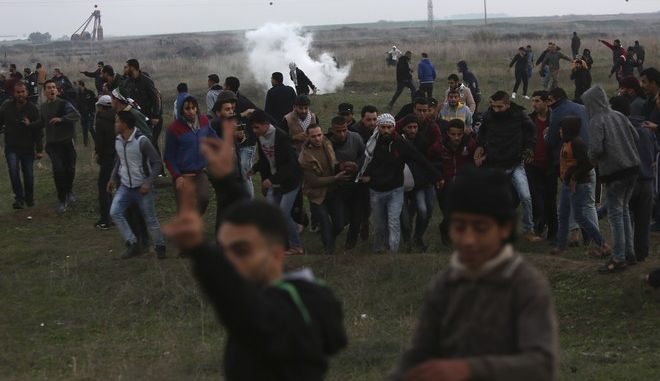 Palestinian protesters evacuate a wounded youth during clashes on the Israeli border following a protest against U.S. President Donald Trump's decision to recognize Jerusalem as the capital of Israel, east of Gaza City, Friday, Dec. 29, 2017. (AP Photo/Adel Hana)