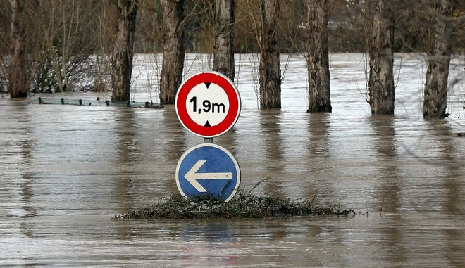 A road sign visible on a flooded road in Peyrorade, southwestern France, caused by heavy rains, Saturday, Dec. 14, 2019. Southwestern France is on alert for violent storms, high winds and floods. (AP Photo/Bob Edme)