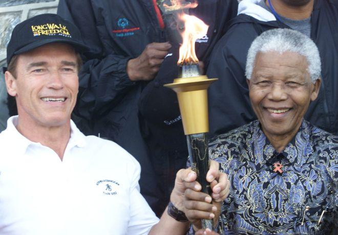 Former President Nelson Mandela and actor Arnold Schwarzenegger hold a symbolic
