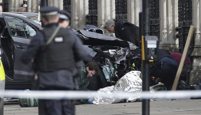 Emergency personnel tend to an injured person close to the Palace of Westminster, London, Wednesday, March 22, 2017.  London police say officers called to a 'firearms incident' on Westminster Bridge, near Parliament. The leader of Britain's House of Commons says a man has been shot by police at Parliament. David Liddington also said there were