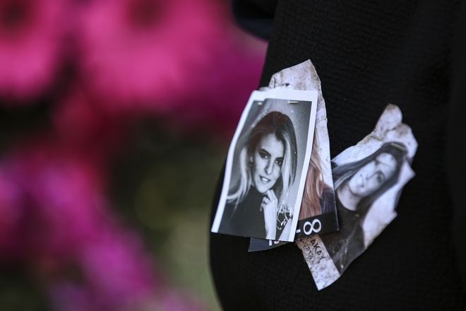 Family members hold images of Mina Basaran, left, and Sinem Akay during funeral prayers in Istanbul, Thursday, March 15, 2018. Funerals have been held for nine out of the 11 victims from a private Turkish jet that crashed in Iran while flying a bride-to-be and her friends back to Istanbul from a bachelorette party in the United Arab Emirates. Mina Basaran, the 28-year-old daughter of the chairman of Turkey's Basaran Investment Holding, was killed along with her seven friends, and three female crew members.(AP Photo/Emrah Gurel)