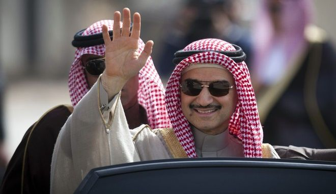 FILE - In this Feb. 4, 2014 file photo, Saudi billionaire Prince Alwaleed bin Talal, waves as he arrives at the headquarters of Palestinian President Mahmoud Abbas in the West Bank city of Ramallah.  Saudi Arabia has arrested dozens of princes and former government ministers, including a well-known billionaire with extensive holdings in Western companies, as part of a sweeping anti-corruption probe, further cementing King Salman and his crown prince son's control of the kingdom. A high-level employee at Prince Alwaleed bin Talal's Kingdom Holding Company told The Associated Press that the royal was among those detained overnight Saturday, Nov. 4, 2017. (AP Photo/Majdi Mohammed, File)