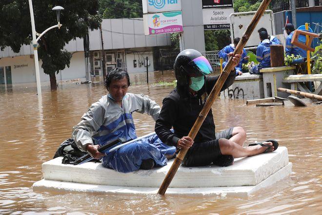 Οι κάτοικοι χρησιμοποιούν ένα φελλό ως σχεδία για να περάσουν από πλημμύρες, 20 Φεβρουαρίου 2021, στην Τζακάρτα της Ινδονησίας.