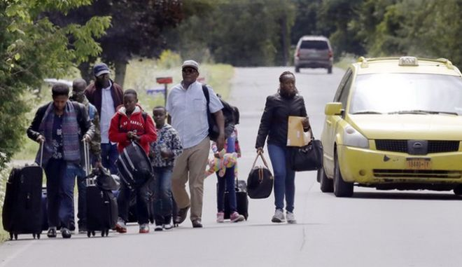 Migrants wheel their luggage down Roxham Road in Champlain, N.Y., while heading to an unofficial border station across from Saint-Bernard-de-Lacolle, Quebec, Monday, Aug. 7, 2017. Officials on both sides of the border first began to notice last fall, around the time of the U.S. presidential election, that more people were crossing at Roxham Road. Since then the numbers have continued to climb. (AP Photo/Charles Krupa)