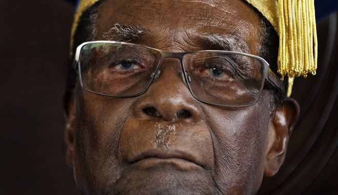 FILE - In this Friday Nov. 17, 2017 file photo, Zimbabwean President Robert Mugabe attends a graduation ceremony on the outskirts of Harare. A Zimbabwe ruling party official confirmed Sunday, Nov. 19 2017 that the Central Committee has fired Mugabe as party leader and replaced him with the recently dismissed Vice President, Emmerson Mnangagwa. (AP Photo/Ben Curtis, File)