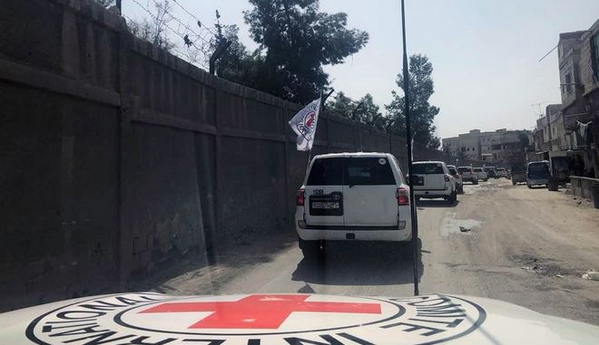 This photo release by the International Committee of The Red Cross, shows a convoy of the Red Cross vehicles headed to eastern Ghouta, a suburb of Damascus, Syria, Monday, March. 5, 2018. Desperate for food and basic medicines, many of the besieged and bombarded Syrian civilians in Damascus' eastern suburbs of Ghouta awaited Monday for a 46-truck convoy organized by the United Nations and key aid agencies to enter the rebel-held enclave. (International Committee of The Red Cross via AP)
