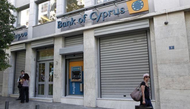 Πολίτες περπατούν έξω από υποκατάστημα της τράπεζας Κύπρου, στην Αθήνα, τη Δευτέρα 20 Αυγούστου 2012.Το ενδεχόμενο να προχωρήσει σε ανταλλαγή στοιχείων ενεργητικού με ελληνική τράπεζα που δραστηριοποιείται στην Κύπρο, εξετάζει η διοίκηση της Τράπεζας Κύπρου, όπως επισημαίνεται σε σημερινή της ανακοίνωση στο Χρηματιστήριο Αθηνών. Σύμφωνα με δημοσιεύματα κατά τα οποία το Συγκρότημα της Τράπεζας Κύπρου φέρεται να προχωρεί σε ανταλλαγή περιουσιακών στοιχείων με άλλον τραπεζικό οργανισμό, το Συγκρότημα διευκρινίζει στην ανακοίνωσή του ότι στο πλαίσιο του ευρύτερου προγραμματισμού του για ενίσχυση της κεφαλαιακής του θέσης, καθώς και θωράκισης του ισολογισμού του, εξετάζει αριθμό επιλογών. ΑΠΕ-ΜΠΕ/ΑΠΕ-ΜΠΕ/ΑΛΚΗΣ ΚΩΝΣΤΑΝΤΙΝΙΔΗΣ