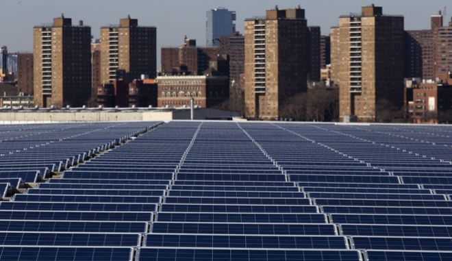 A rooftop is covered with solar panels at the Brooklyn Navy Yard, Tuesday, Feb. 14, 2017, in New York. In the background are apartment buildings in Manhattan. ConEdison Solutions installed 3,152 solar panels on the roof of Building 293 in 2016. The new panels will generate 1.1 million kilowatt hours of energy per year, according to the mayor's office. The New York State Energy Research and Development Authority provided more than $600,000 in incentives for the project. (AP Photo/Mark Lennihan)