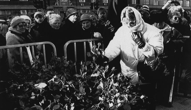 A woman tucks her rose into the growing mound of flowers with scores of people lining up behind her at the spot where Swedish Premier Olof Palme was assassinated one year ago in Stockholm, Sweden on Saturday, Feb. 28, 1987.  (AP Photo/Peter Kjelleras)