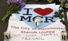 A sign is seen with flowers and candles after a vigil in Albert Square, Manchester, England, Tuesday May 23, 2017, the day after the suicide attack at an Ariana Grande concert that left 22 people dead as it ended on Monday night. (AP Photo/Kirsty Wigglesworth)