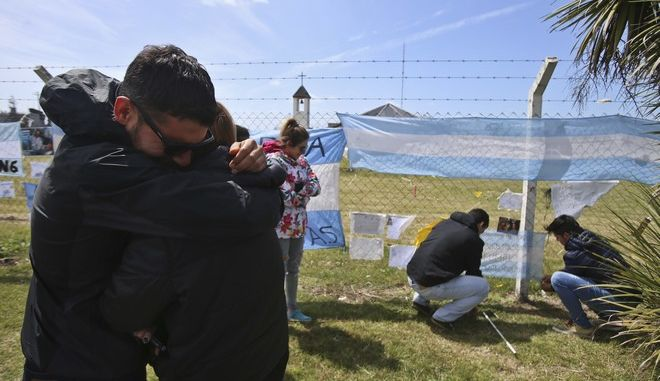 Relatives and friends of Alejandro Tagliaprieta, a crew member on the missing ARA San Juan submarine, embrace at the naval base where people hang flags and messages on the fence in Mar de Plata, Argentina, Friday, Nov. 24, 2017. The navy says an explosion occurred near the time and place where the sub went missing on Nov. 15. That's led some to give up hope. (AP Photo/Esteban Felix)