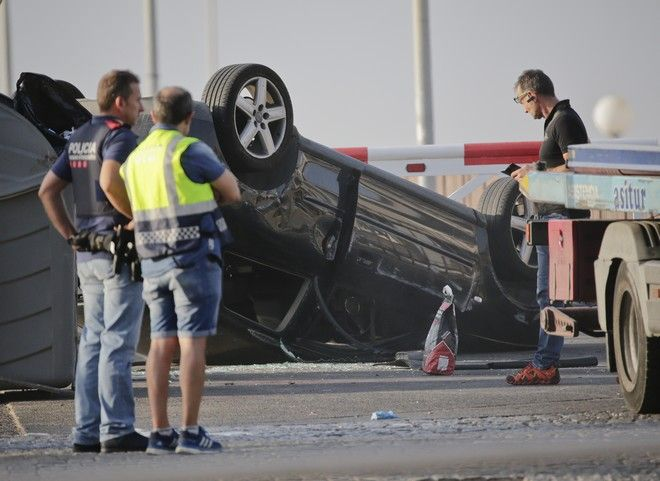 Police officers stand near an overturned car onto a platform at the spot where terrorists were intercepted by police in Cambrils, Spain, Friday, Aug. 18, 2017. The police force for Spain's Catalonia region says the five suspects shot and killed in the resort town of Cambrils were carrying bomb belts, which have been detonated by the force's bomb squad. (AP Photo/Emilio Morenatti)