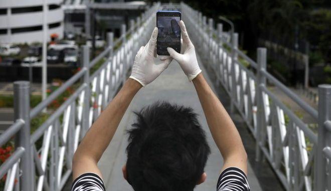 Άνθρωπος φορά γάντια κρατώντας το κινητό