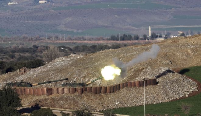 """In this photo taken Friday, Jan. 19, 2018, Turkish artillery fire toward Syrian Kurdish positions from the Turkish side of the border, in Hatay, southern Turkey. Turkey's President Recep Tayyip Erdogan repeated Saturday that a Turkish offensive against the Syrian Kurdish-controlled enclave of Afrin was """"de facto"""" underway and said it would be followed by an operation against another Kurdish-held territory.(Nuri Pir/IHA via AP)"""
