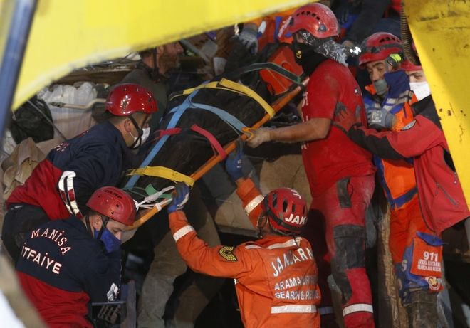 Members of rescue services remove a body of a victim from the debris of a collapsed building in Izmir, Turkey, early Saturday, Oct. 31, 2020. Rescue teams on Saturday ploughed through concrete blocs and debris of eight collapsed buildings in Turkey's third largest city in search of survivors of a powerful earthquake that struck Turkey's Aegean coast and north of the Greek island of Samos, killing dozens and injured scores of others. (AP Photo/Darko Bandic)