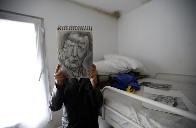 "Farhad Nouri poses with a portrait of German Chancellor Angela Merkel in his room in the ""Krnjaca"" collective centre near Belgrade, Serbia, Monday, March 13, 2017. A 10-year-old boy from Afghanistan is known as Little Picasso among migrants in a Serbia asylum camp because of his artistic talent. Nouri, his parents and two younger brothers hope to move to Switzerland or the United States, but have been stuck in the Balkan country for months unable to cross the heavily guarded borders of the European Union. (AP Photo/Darko Vojinovic)"