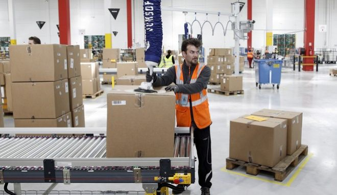 An Amazon employee works during the visit of French President Emmanuel Macron at the new Amazon warehouse in Boves, northern France, Tuesday, Oct. 3, 2017. (Yoan Valat/Pool Photo via AP)