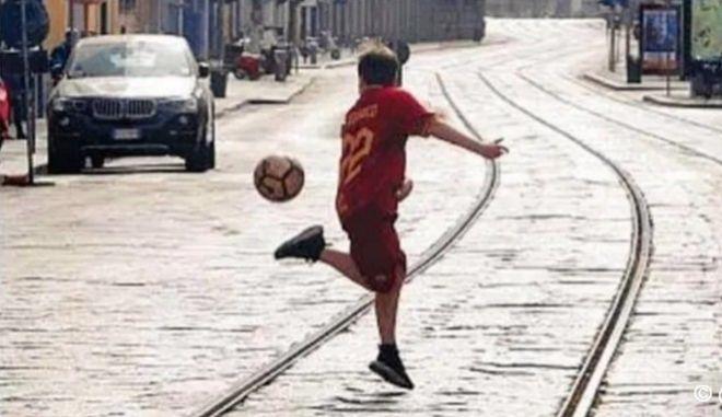 Παιδί με φανέλα της Ρόμα παίζει μπάλα σε έρημο δρόμο του Μιλάνου