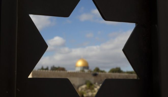 The Dome of the Rock Mosque in the Al Aqsa Mosque compound in Jerusalem's Old City is seen trough a door with the shape of star of David, Thursday, Dec. 7, 2017, a day after U.S. President Donald Trump's recognition of Jerusalem as Israel's capital. (AP Photo/Ariel Schalit)