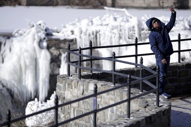 Obdulio Arenas, of Paterson, N.J., uses a cell phone to capture a selfie in front of the partially frozen falls at the Paterson Great Falls National Historical Park, Tuesday, Jan. 2, 2018, in Paterson, N.J. The Northern New Jersey region continued to experienced deep cold weather to start the new year. (AP Photo/Julio Cortez)
