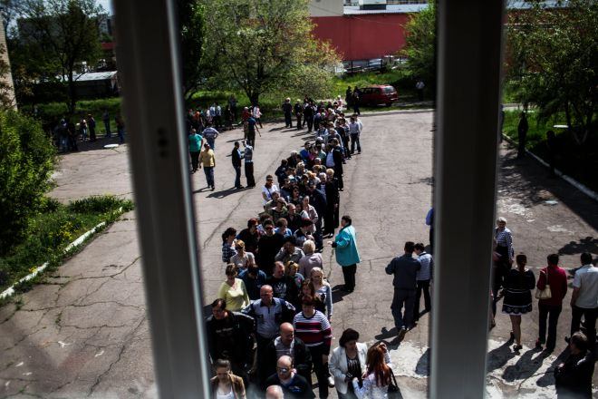Ukrainians line up to cast their votes at a polling station in the Budennovskiy district, on the outskirts of Donetsk, Ukraine, Sunday May 11, 2014. Residents of two restive regions in eastern Ukraine engulfed by a pro-Russian insurgency are casting ballots in contentious and hastily organized independence referenda. Sunday's ballots seek approval for declaring so-called sovereign people's republics in the Donetsk and Luhansk regions, where rebels have seized government buildings and clashed with police and Ukrainian troops. (AP Photo/Manu Brabo)