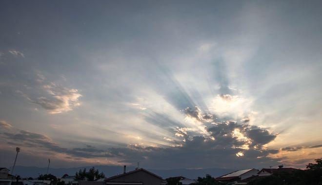 Οι ακτίνες του ηλίου ξεπροβάλουν μέσα από τα συννέφα πάνω από την πόλη των Τρικάλων.