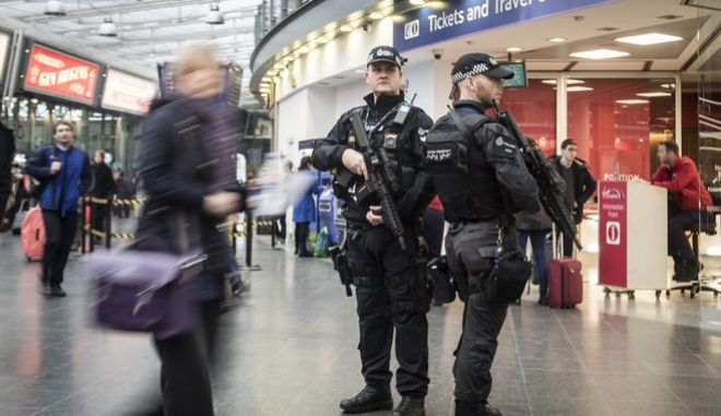 """Armed British Transport Police officers patrol Manchester Piccadilly transport hub in Manchester, England, Tuesday Dec. 19, 2017.  The force announced Tuesday that it will have new units with firearms officers, specialist support dogs and """"behaviour detection"""" personnel based in Birmingham and Manchester, for the first time based outside of London. (Danny Lawson/PA via AP)"""