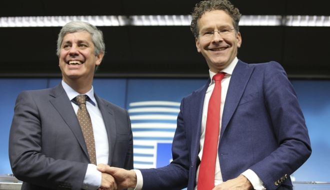 Portugal's Finance Minister Mario Centeno, left, shakes hands with president of the eurogroup Jeroen Dijsselbloem during a media conference after a meeting of eurozone finance ministers at the Europa building in Brussels on Monday, Dec. 4, 2017. The Eurogroup on Monday elected Portugal's Finance Minister Mario Centeno as the new president of the Eurogroup. (AP Photo/Olivier Matthys)