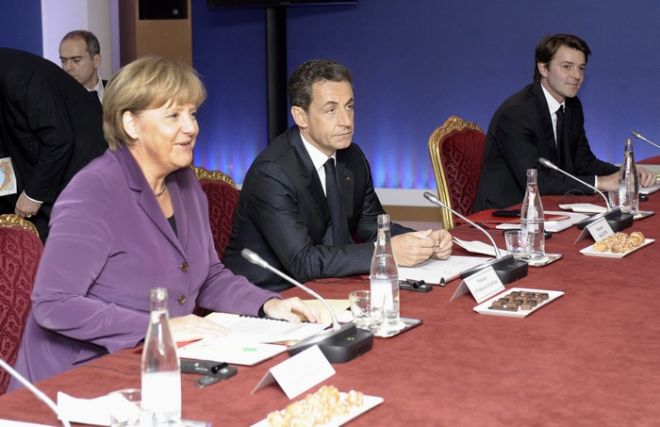 epa02989746 French President Nicolas Sarkozy (C), and German Chancellor Angela Merkel (L), meet during the emergency meeting in order to discuss the new developments regarding the Greek crisis, one day before the start of the G-20 summit, in Cannes, France, 02 November 2011. Greek government has triggered concerns after having announced they will submit to a referendum the EU plan to rescue Greece from default.  EPA/CHRISTOPHE KARABA / POOL