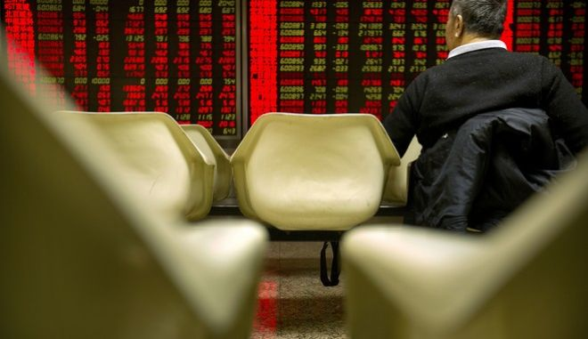 An investor monitors stock prices in a brokerage house in Beijing, Tuesday, Jan. 2, 2018. Asian stock markets were mostly higher Tuesday as 2018 trading began and investors looked ahead to whether the record-setting U.S. equity run will last. (AP Photo/Mark Schiefelbein)