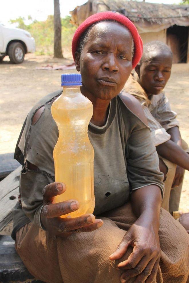 Η Esther Nalumgwe 64 ετών, κρατάει μπουκάλι με το μολυσμένο νερό από την πηγή της περιοχής.