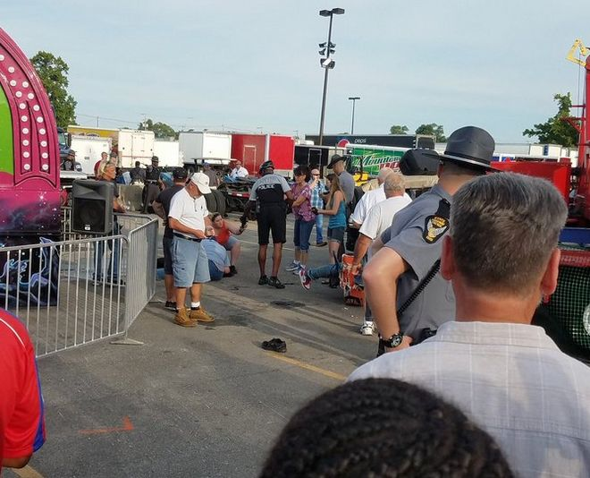 A person is attended to as authorities respond after the Fire Ball amusement ride malfunctioned injuring several at the Ohio State Fair, Wednesday, July 26, 2017, in Columbus, Ohio. Columbus Fire Battalion Chief Steve Martin said that some of the victims were thrown from the ride when it malfunctioned Wednesday night. (Justin Eckard via AP)
