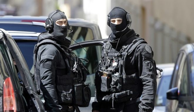Hooded police officers patrol outside a building during searches in Marseille, southern France, Tuesday, April 18, 2017. Security concerns shook France's presidential campaign Tuesday as authorities announced arrests in a thwarted attack on the eve of the vote, and candidates urged tougher counterterrorism efforts for a country already under a state of emergency. (AP Photo/Claude Paris)