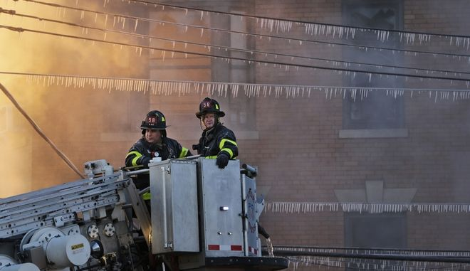 Icicles hang off power lines as firefighters work to contain a blaze at a building in the Bronx section of New York, Tuesday, Jan. 2, 2018. (AP Photo/Seth Wenig)