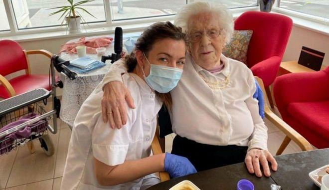 Η ηλικιωμένη αγκαλιά με εργαζόμενη του γηροκομείου