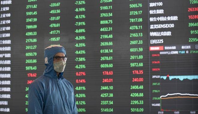 Άνδρας με μάσκα μπροστά από πίνακα χρηματιστηριακών συναλλαγών στη Σαγκάη