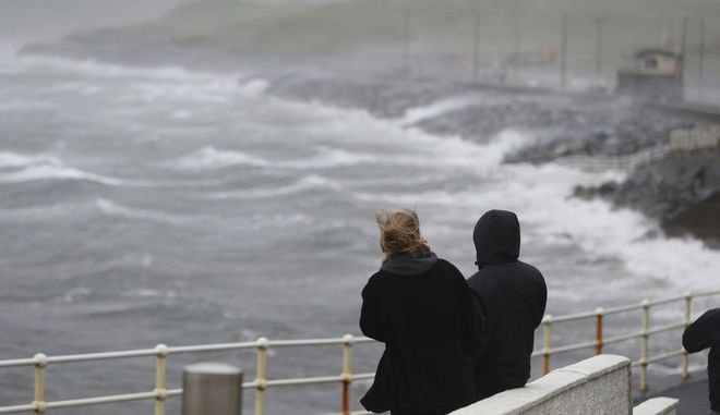 People watch the waves and sea spray at Lahinch  on the west coast of Ireland  Monday Oct. 16, 2017, as the remnants of  Hurricane Ophelia begins to hit Ireland and parts of Britain. Ireland's meteorological service is predicting wind gusts of 120 kph to 150 kph (75 mph to 93 mph), sparking fears of travel chaos. Some flights have been cancelled, and aviation officials are warning travelers to check the latest information before going to the airport Monday.  (Niall Carson/PA via AP)