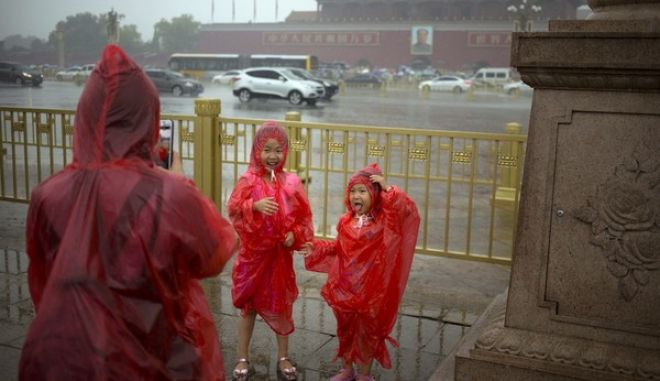 Children wearing rain ponchos pose for a photo on Tiananmen Square on a rainy day in Beijing, Thursday, July 6, 2017. Although China's capital is in a semi-dry climate, it receives much of its annual precipitation during the summer months. (AP Photo/Mark Schiefelbein)
