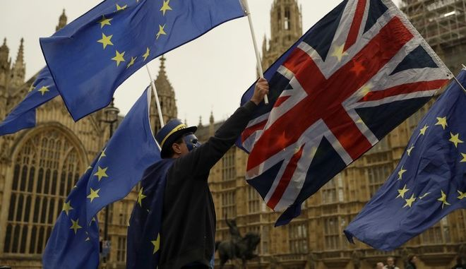 Pro-EU supporters hold European Union flags with a Union flag across the street from the Houses of Parliament in London, Tuesday, Oct. 17, 2017. (AP Photo/Matt Dunham)