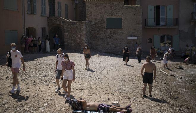 Τουρίστες με μάσκες λόγω κορονοϊού στο Σεν Τροπέ τον Αύγουστο του 2020