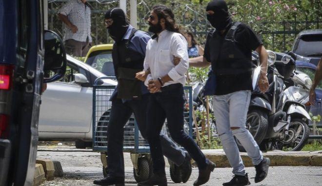 Ο Κώστας Μπαρμπαρούσης οδηγείται ενώπιον του ανακριτή από αστυνομικούς προκειμένου να απολογηθεί για το κακουργηματικού βαθμού αδίκημα των προπαρασκευαστικών πράξεων εσχάτης προδοσίας