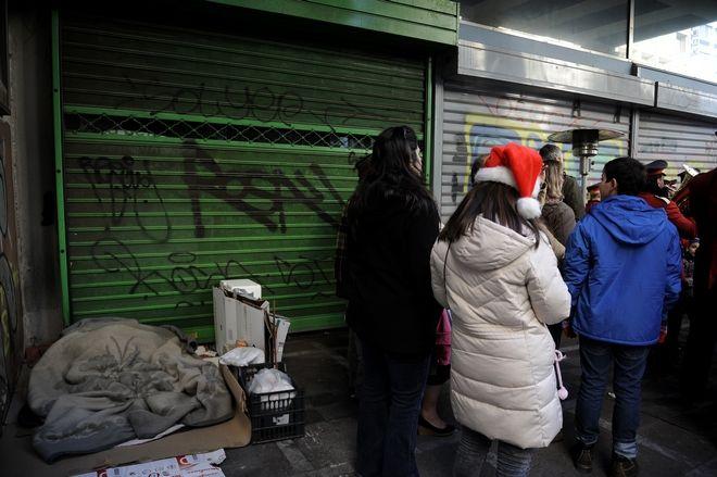 Λίγα μόλις μέτρα απόσταση από την μικρή γιορτή που οργανώθηκε από τον Δήμο Αθηναίων,απέναντι από τον καμένο κινηματογράφο Αττικόν και μπροστά από ένα κλειστό ξενοδοχείο που έκλεισε στα χρόνια της κρίσης,το Εσπέρια,τα αυτοσχέδια κρεβάτια τριών αστέγων.Οι χριστουγεννιάτικες μπάλες στα χαρτόκουτα και οι ήχοι από τα κάλαντα και τα χριστουγεννιάτικα τραγούδια,ήταν μια αντίφαση,Σάββατο 24 Δεκεμβρίου 2016 (EUROKINISSI/ΤΑΤΙΑΝΑ ΜΠΟΛΑΡΗ)