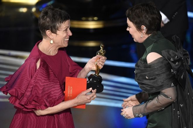 Frances McDormand, left, presents Olivia Colman with the award for best performance by an actress in a leading role for