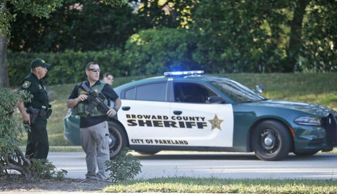 Law enforcement officers block off a street following a shooting at Marjory Stoneman Douglas High School, Wednesday, Feb. 14, 2018, in Parkland, Fla. (AP Photo/Wilfredo Lee)