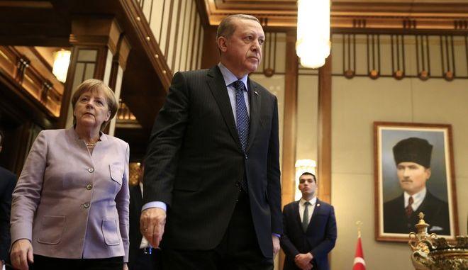 German Chancellor Angela Merkel, left, and Turkish President Recep Tayyip Erdogan, center, arrive for a press statement after a meeting in Ankara, Turkey, Thursday, Feb. 2, 2017. (AP Photo/Lefteris Pitarakis)