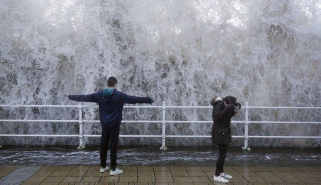 Children stand on the seafront as a wave crashes over the sea wall in Aberystwyth in west Wales as Storm Eleanor lashed Britain with violent storm-force winds of up to 100mph, leaving thousands of homes without power and hitting transport links Wednesday Jan. 3, 2018. (Aaron Chown/PA via AP)